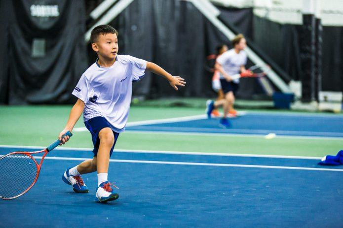 Jeune Garcon Concentré Sur Sa Technique Durant Un Cours De Tennis Canada Kids
