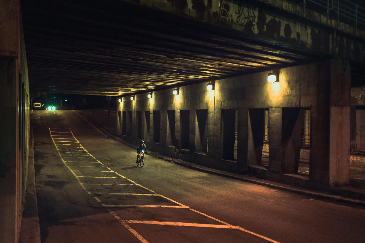 Cycliste sur vélo de route Opus sous un viaduc la nuit